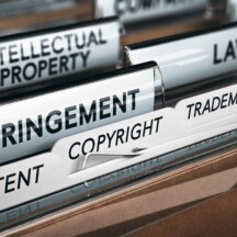 Row of files each displaying a word relating to copyright law - Intelectual property, law, infringement, patent, trademark
